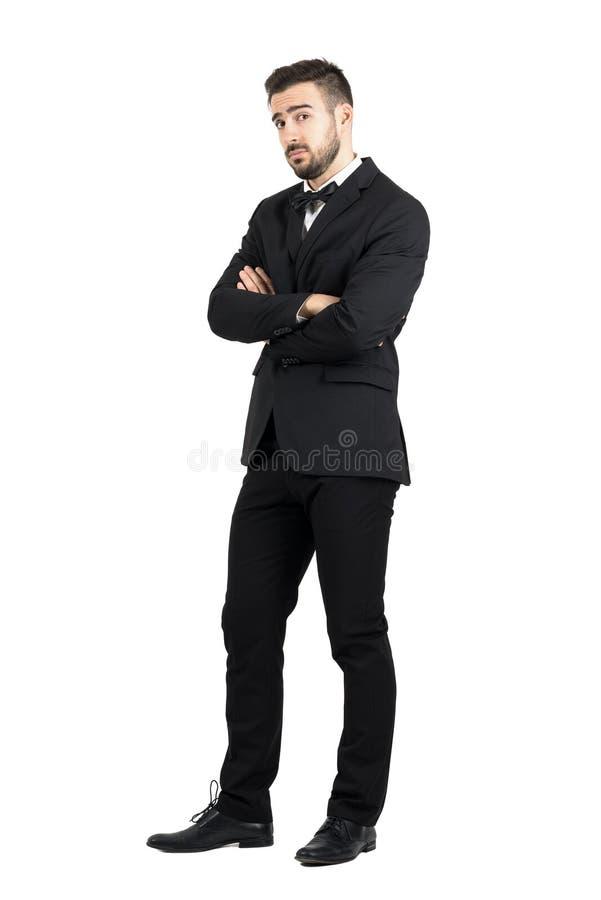 Uomo difensivo scettico con le armi attraversate che esaminano sospettoso macchina fotografica fotografia stock libera da diritti