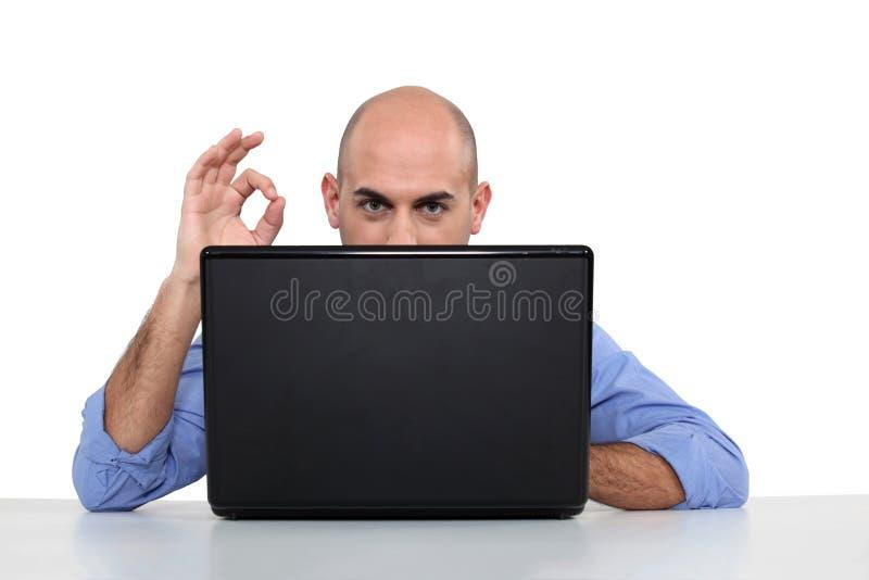 Uomo difettoso con il computer portatile fotografia stock