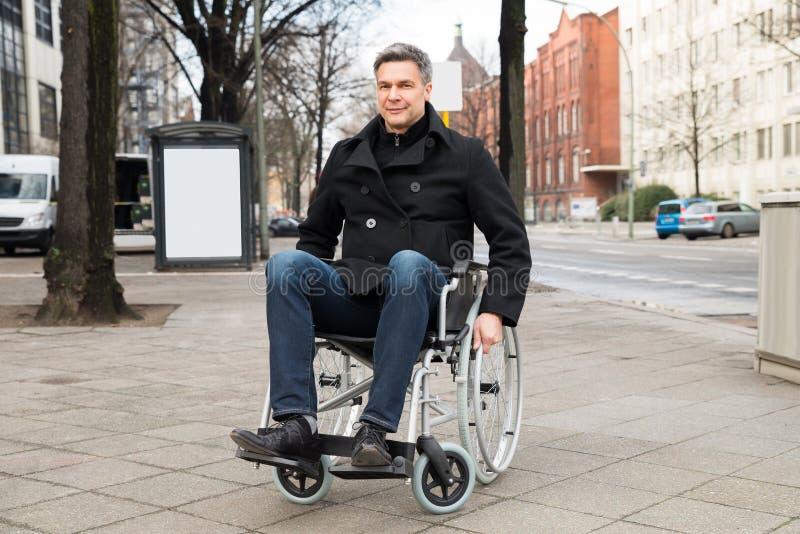 uomo disabile sulla sedia a rotelle in citt immagine