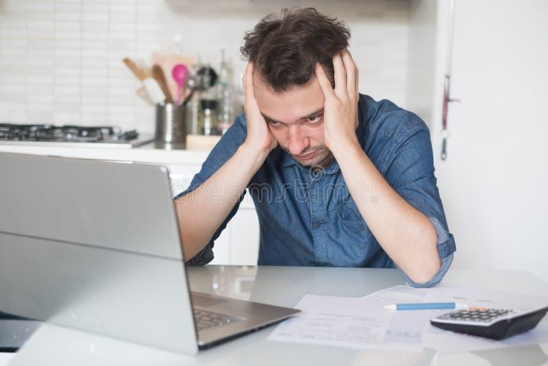 Uomo disperato che prova a trovare soluzione per le tasse e le fatture immagini stock libere da diritti