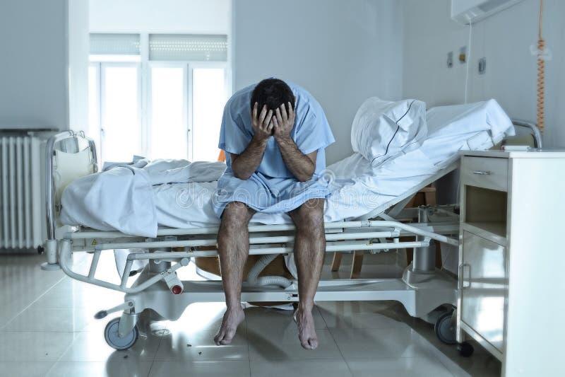 Uomo disperato che si siede di ospedale del letto alla s triste e devastante da solo immagine stock