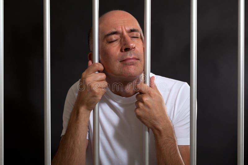 Uomo disperato e triste dietro le barre fotografie stock libere da diritti