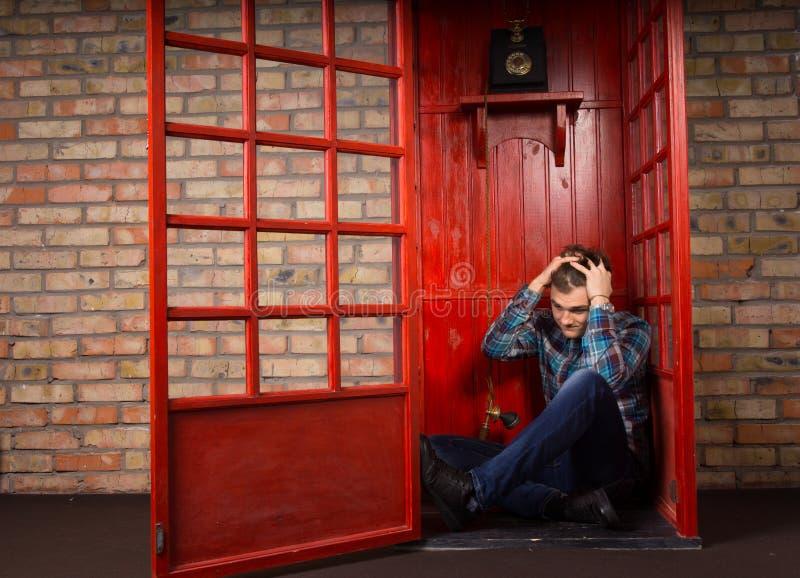 Uomo disturbato che si siede sul pavimento della cabina telefonica fotografia stock