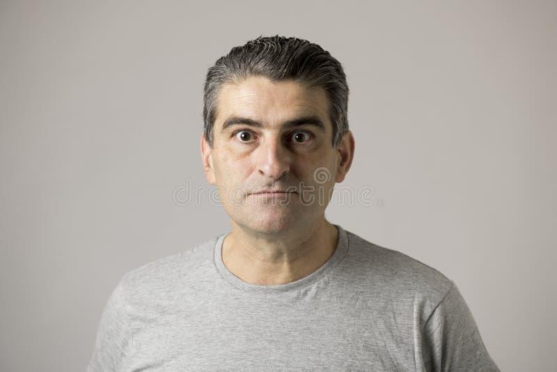 Uomo divertente bianco non attraente 40s o 50s nell'espressione sconosciuta malata e pazza del fronte isolato su fondo grigio fotografie stock