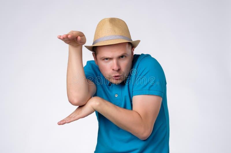 Uomo divertente in cappello di estate che alza palma come se conoscendo kung-fu fotografia stock
