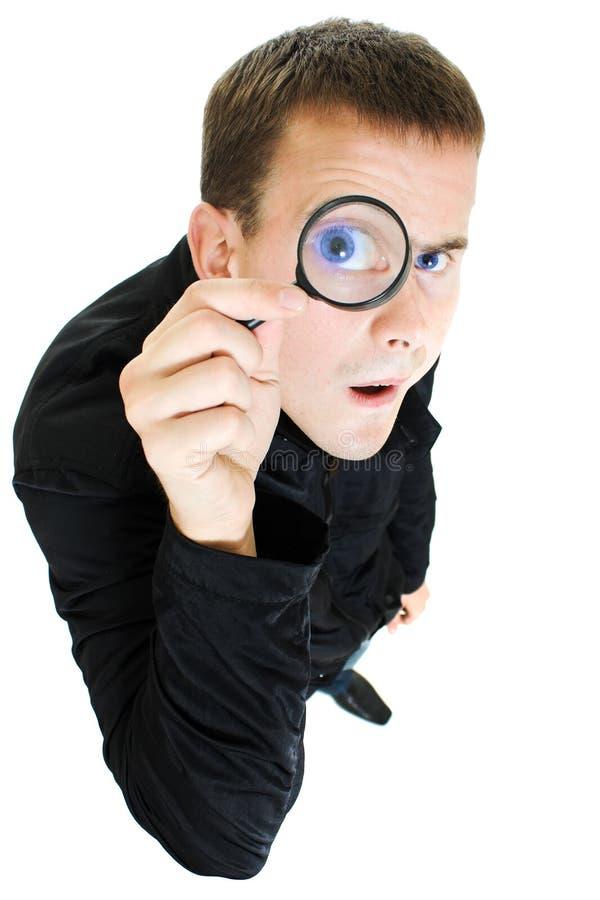 Uomo divertente che osserva tramite una lente d'ingrandimento. immagini stock