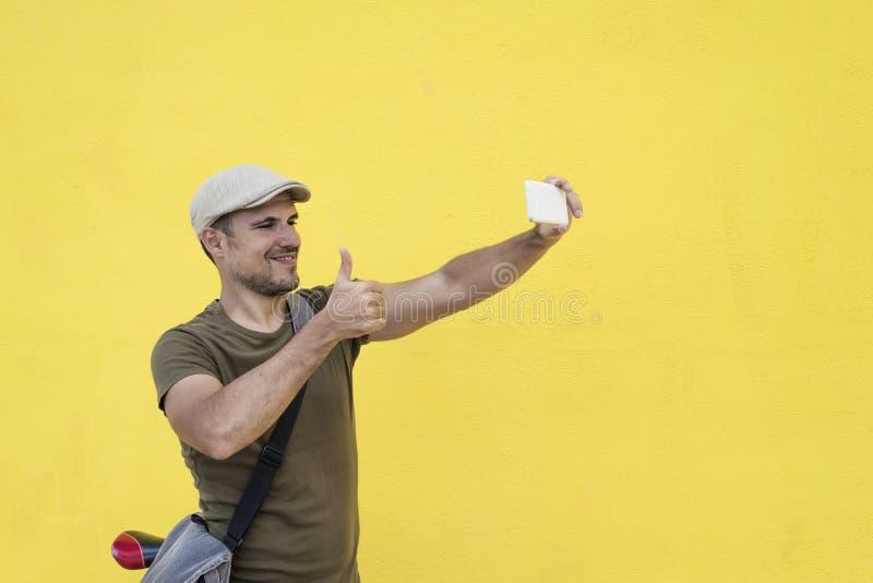 Uomo divertente che prende selfie e che mostra pollice su fotografia stock libera da diritti