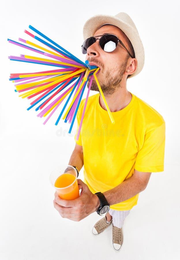 Uomo divertente che tiene un vetro dei vetri di sole d'uso del succo e della maglietta gialla su bianco immagini stock libere da diritti