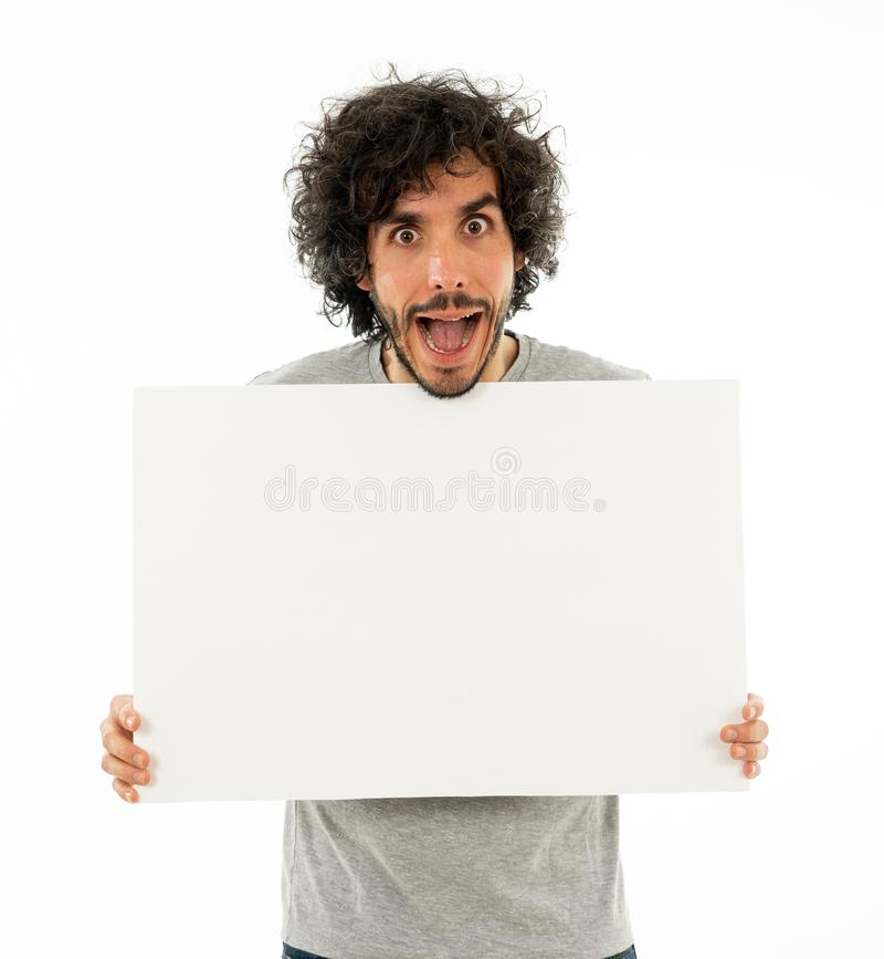 Uomo divertente giovane che tiene bordo in bianco per la pubblicità Uomini millenari che indicano al tabellone per le affissioni  fotografia stock