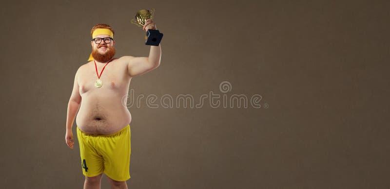 Uomo divertente spesso con una tazza di campionato in sue mani fotografia stock libera da diritti