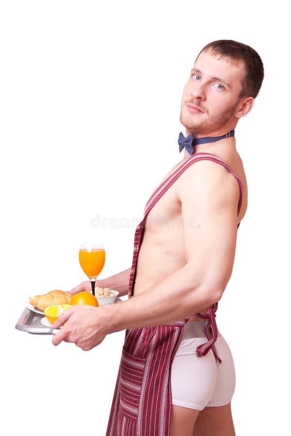 Uomo divertente in un grembiule con la prima colazione immagine stock libera da diritti