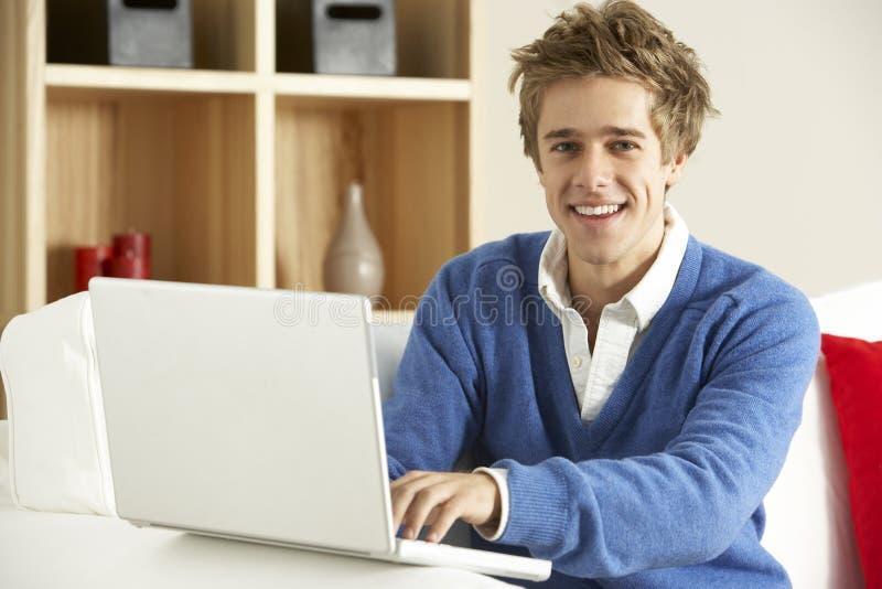 uomo domestico del computer portatile che usando i giovani fotografia stock libera da diritti