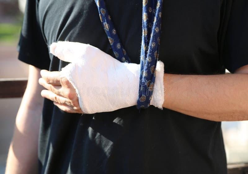 Uomo dopo l'incidente con il suo braccio intorno al suo collo ed alla sua mano fotografie stock