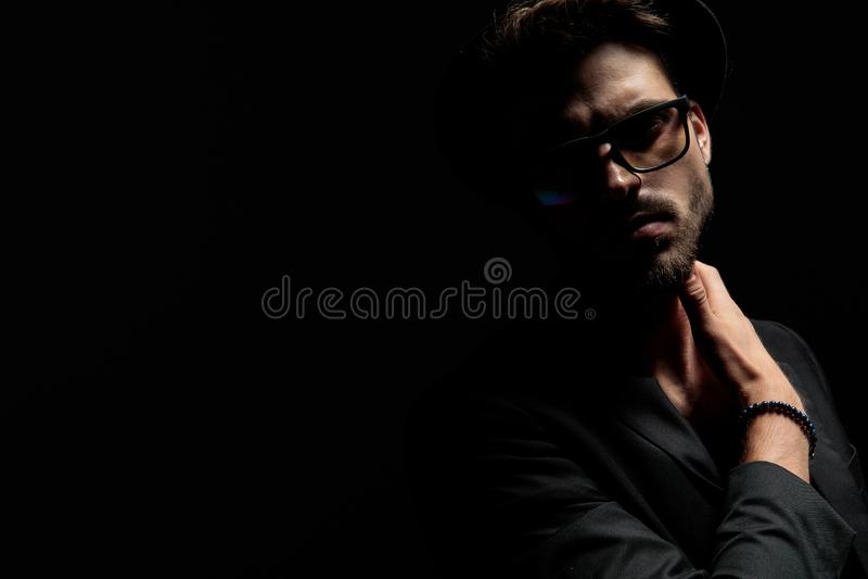 Uomo drammatico bello che tocca il suo collo e che guarda in avanti immagini stock