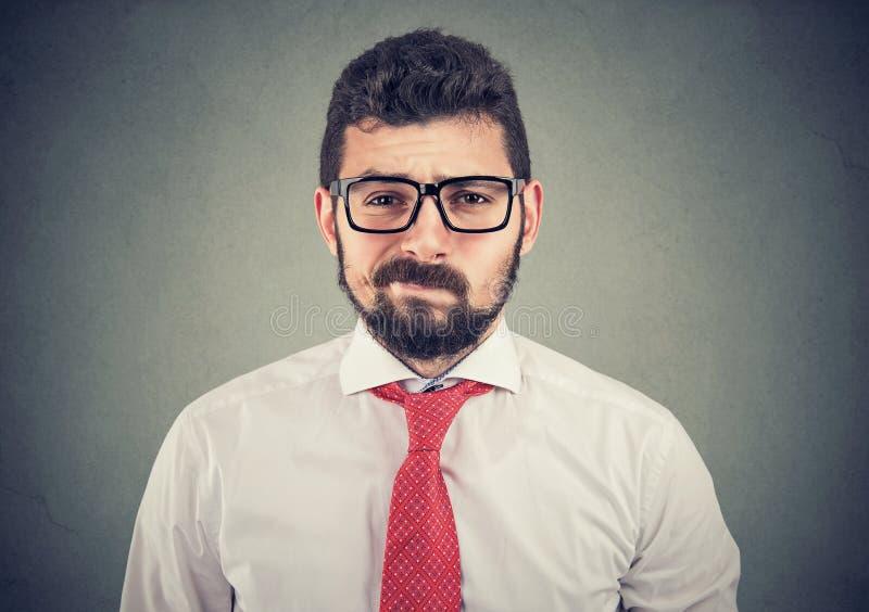 Uomo dubbioso scettico di affari che esamina macchina fotografica immagine stock