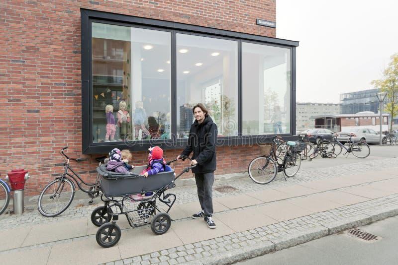 Uomo e bambini in un passeggiatore vicino alle finestre di un asilo fotografia stock