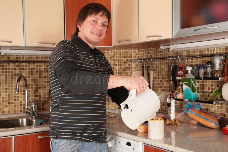 Uomo e caldaia sulla cucina fotografia stock libera da diritti