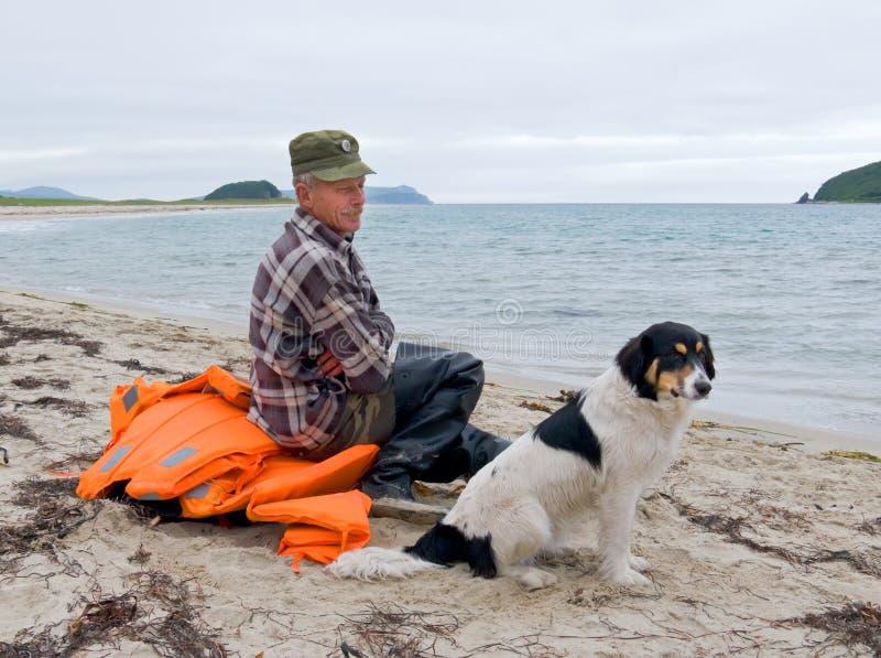 Uomo e cane alla spiaggia 3 immagini stock libere da diritti