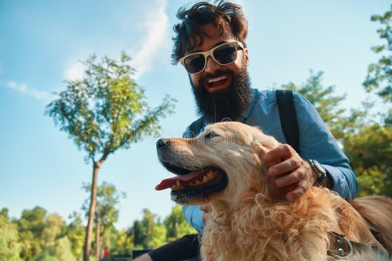 Uomo e cane divertendosi, giocare, facente i fronti divertenti mentre restin immagine stock