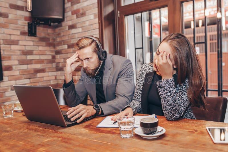 Uomo e donna arrabbiati sollecitati di affari con il computer portatile fotografia stock libera da diritti