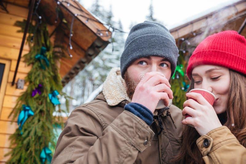 Uomo e donna che bevono caffè caldo sul mercato di natale fotografia stock