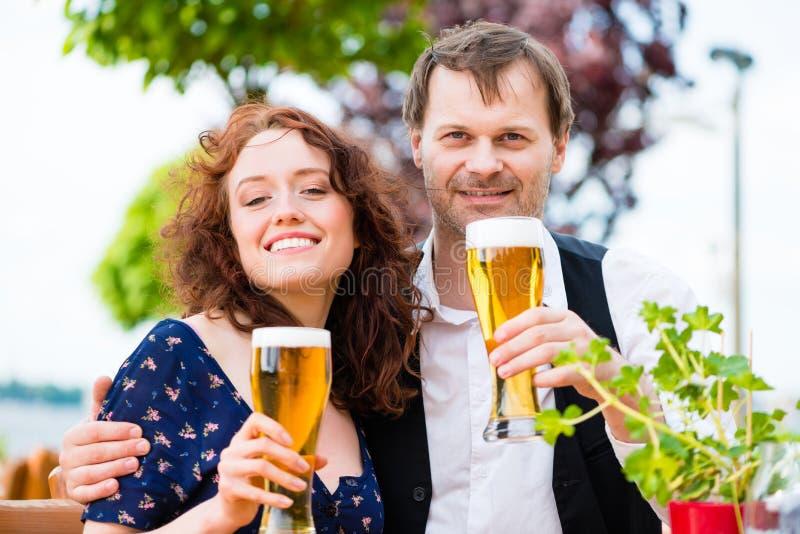 Uomo e donna che bevono nel pub del giardino della birra fotografie stock