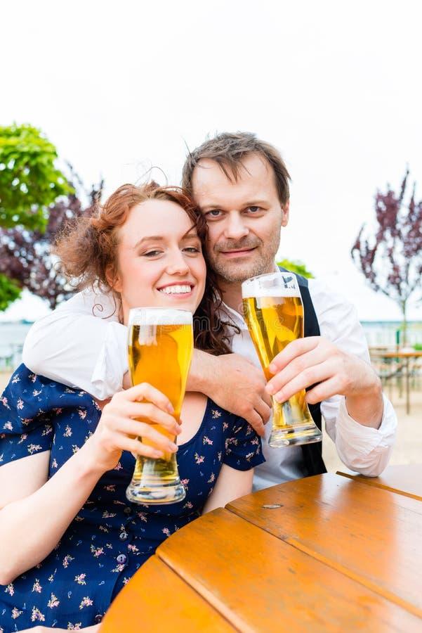 Uomo e donna che bevono nel pub del giardino della birra fotografia stock libera da diritti
