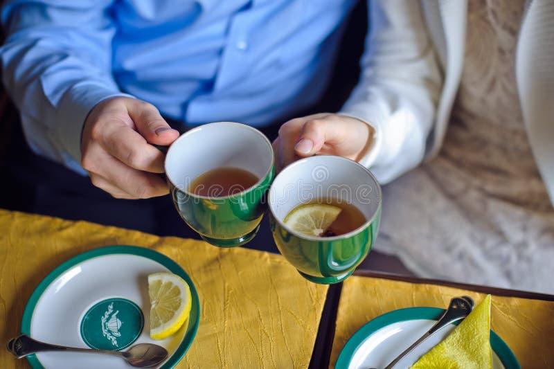 Uomo e donna che bevono tè nero con un limone delle tazze fotografia stock libera da diritti