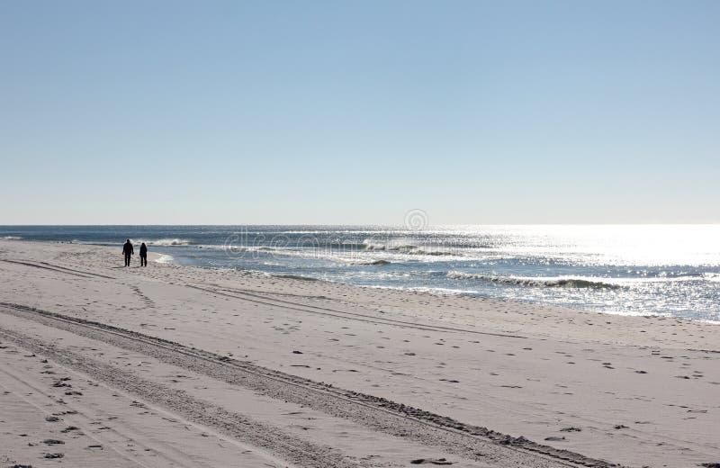 Uomo e donna che camminano sulla spiaggia fotografia stock libera da diritti