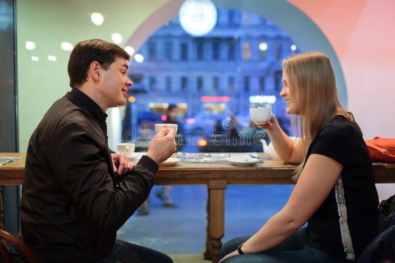 Uomo e donna che chiacchierano sopra il caffè immagine stock