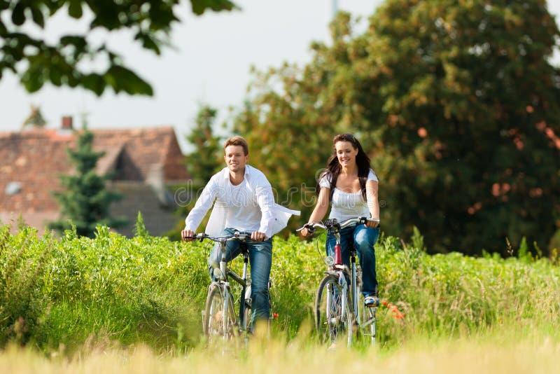 Uomo e donna che ciclano in estate fotografia stock