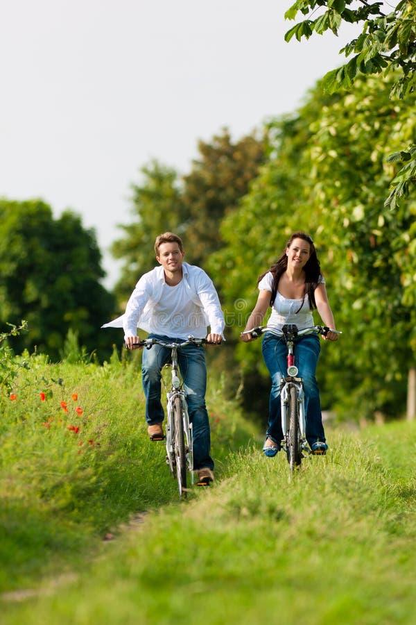 Uomo e donna che ciclano in estate fotografie stock