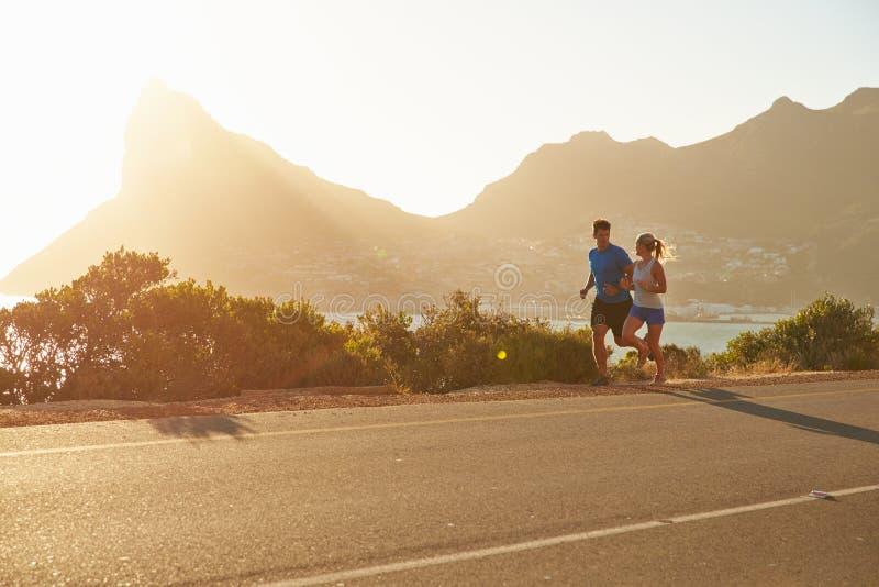 Uomo e donna che corrono insieme su una strada vuota fotografia stock libera da diritti