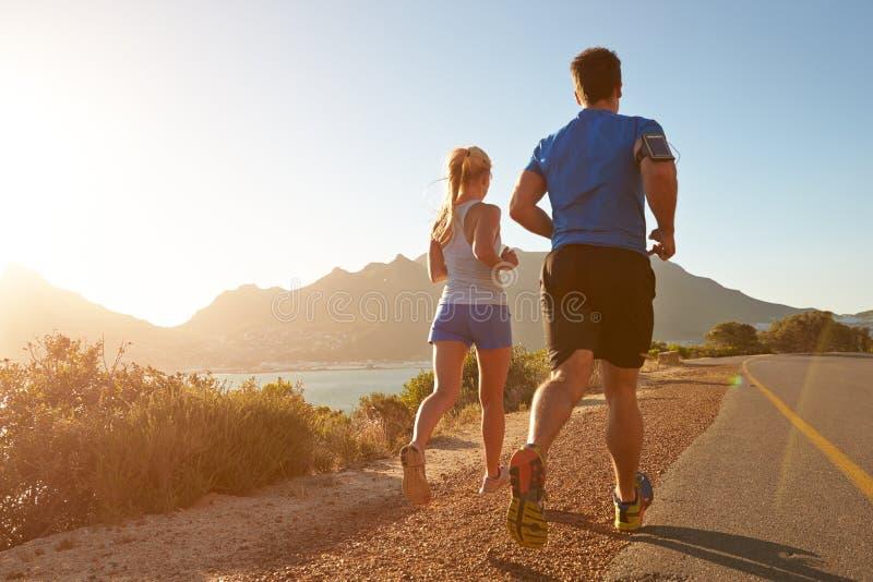 Uomo e donna che corrono insieme su una strada vuota fotografia stock