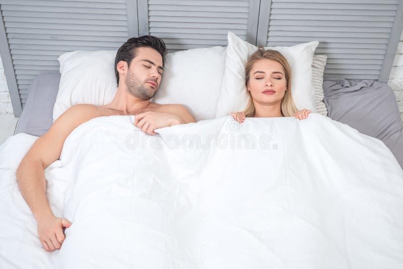 Uomo e donna che dormono nel letto immagini stock libere da diritti