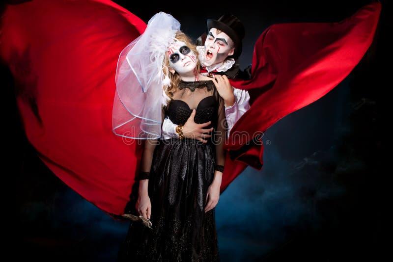 Uomo e donna che durano come il vampiro e strega. Halloween fotografia stock