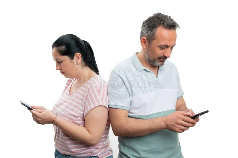 Uomo e donna che esaminano i telefoni fotografia stock