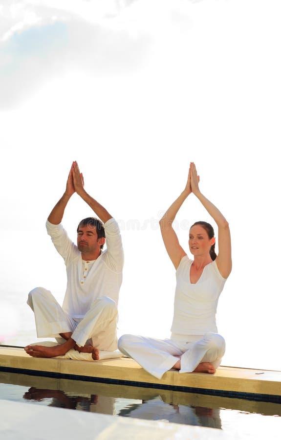 Uomo e donna che fanno yoga vicino al mare immagine stock libera da diritti
