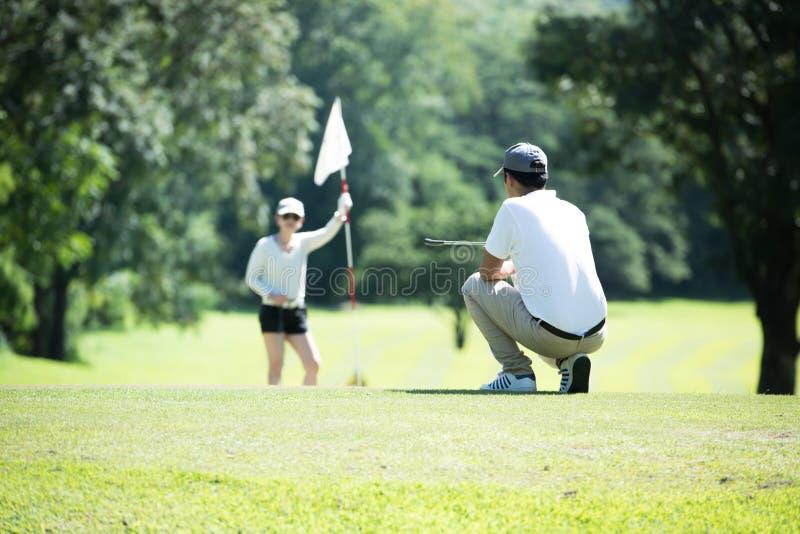 Uomo e donna che giocano golf su un bello campo da golf naturale immagine stock libera da diritti