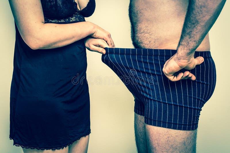 Uomo e donna che guardano giù nella biancheria intima - retro stile immagine stock