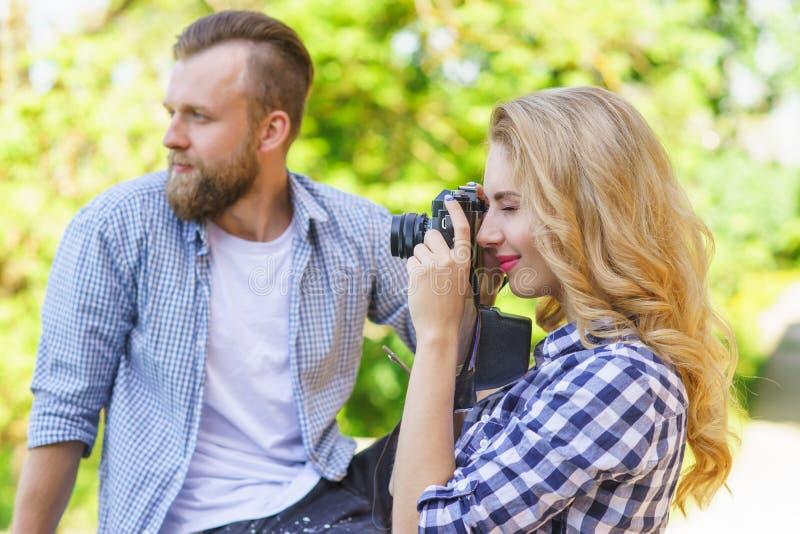 Uomo e donna che hanno data all'aperto Spirito della ragazza una macchina fotografica della foto ed il suo ragazzo fotografie stock libere da diritti
