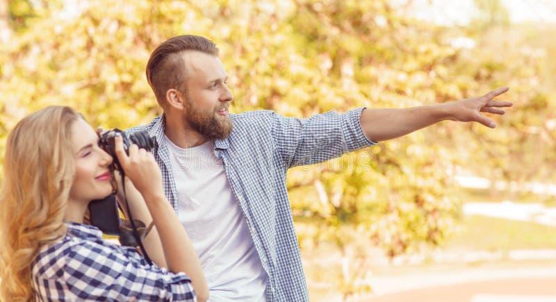 Uomo e donna che hanno data all'aperto Spirito della ragazza una macchina fotografica della foto ed il suo ragazzo immagine stock libera da diritti