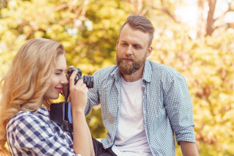 Uomo e donna che hanno data all'aperto Spirito della ragazza una macchina fotografica della foto ed il suo ragazzo fotografia stock libera da diritti