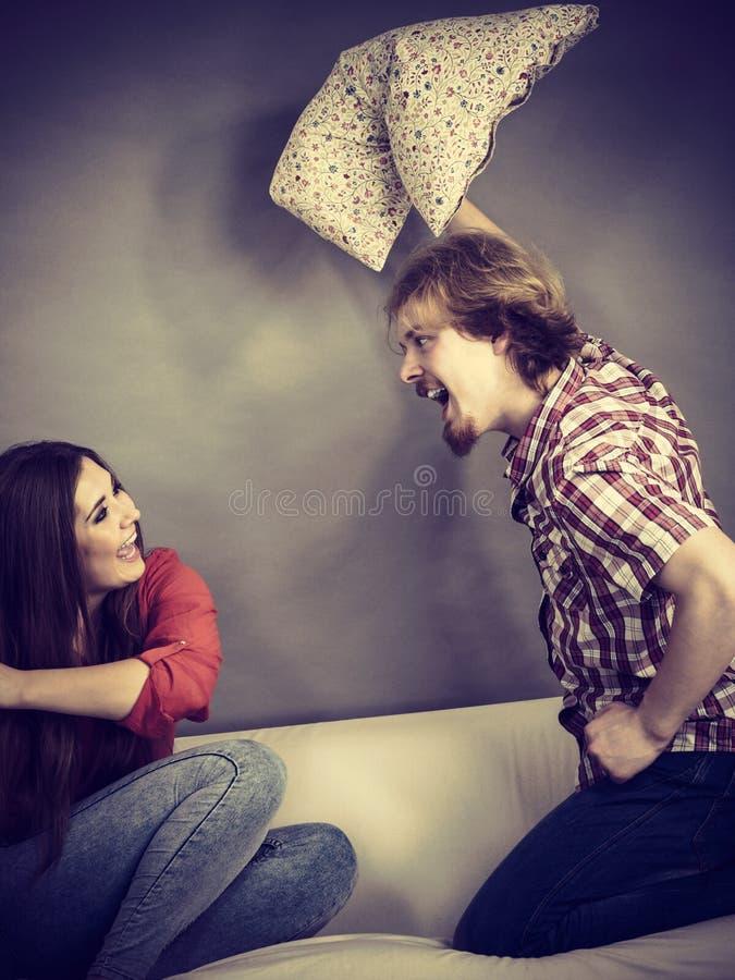 Uomo e donna che hanno lotta di cuscino immagini stock