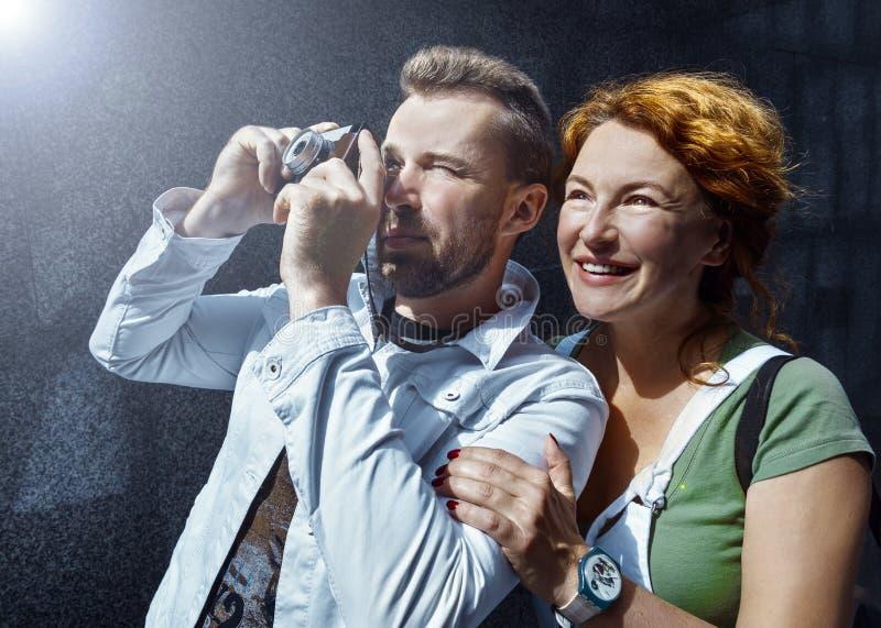 Uomo e donna che prendono immagine sulla macchina fotografica d'annata, giorno, all'aperto fotografie stock