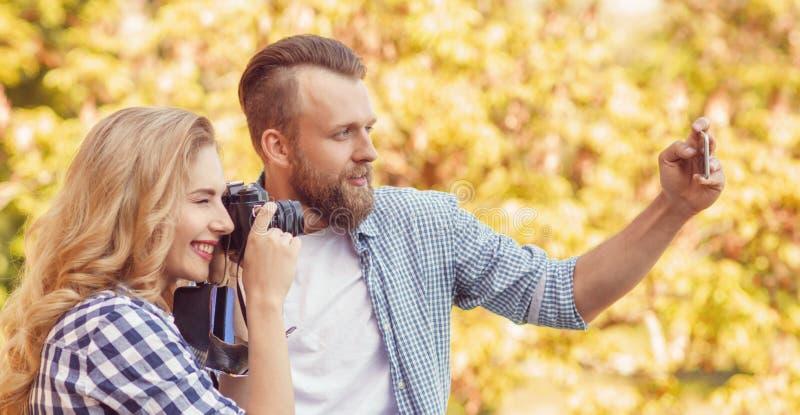 Uomo e donna che prendono le foto con una macchina fotografica e uno smartphone nel parco di autunno fotografie stock libere da diritti
