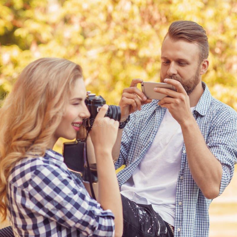 Uomo e donna che prendono le foto con una macchina fotografica e uno smartphone nel parco di autunno immagini stock libere da diritti