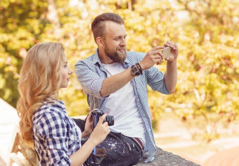 Uomo e donna che prendono le foto con una macchina fotografica e uno smartphone nel parco di autunno fotografia stock libera da diritti