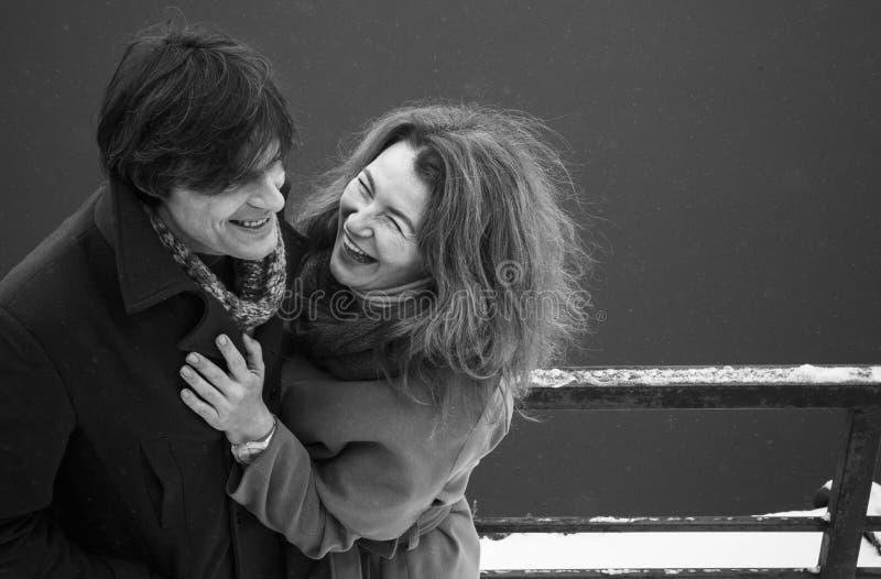 Uomo e donna che ridono insieme, giorno, all'aperto fotografia stock