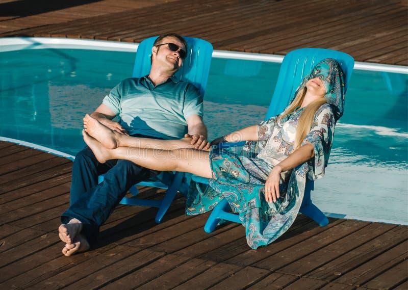 Uomo e donna che si rilassano da uno stagno fotografia stock libera da diritti